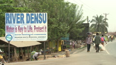 PEDESTRIANS WALK BY DENSU RIVER SIGN Stock Footage