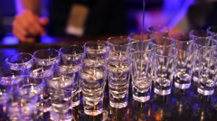 Barman pouring hard spirit into glasses in detail. Stock Footage