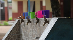 STUDENTS RUN IN TO WATER FAUCETS TO FILL THEIR BRIGHTLY COLORED CUPS Stock Footage