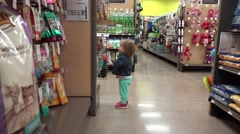 Toddler walking wandering around at pet store aisle looking at goods. DENVER, Stock Footage