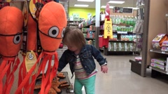 Stock Video Footage of Toddler shopping at pet store at orange stuffed animal dog toy section. DENVER,