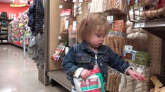 Toddler in jean jacket shopping dog rawhide treats at pet store. DENVER, - stock footage