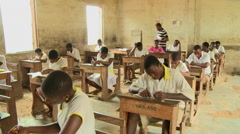 TEACHER WITH STUDENTS AT WOODEN DESKS IN A CLASSROOM - stock footage
