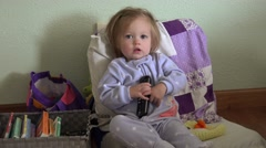 Baby blue pajamas holding tv remote controller seated with books. DENVER, Stock Footage