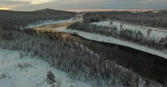 Aerial Shot Of A River Weaving through Snow White Hills With Orange Sunlight Stock Footage