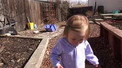 Baby walking outside backyard garden landscaped area smiles. DENVER, COLORADO - stock footage