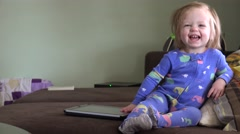 Laughing baby playing with tablet computer on brown couch. DENVER, COLORADO Stock Footage