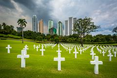 Graves and modern buildings in the distance at the Manila American Cemetery & Stock Photos