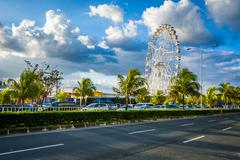Ferris wheel and Seaside Boulevard, in Pasay, Metro Manila, The Philippines. Stock Photos