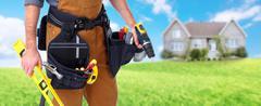 Builder handyman near new house. - stock photo
