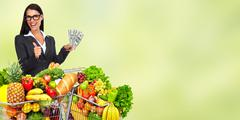 Happy young woman with grocery shopping cart and American dollars. Kuvituskuvat