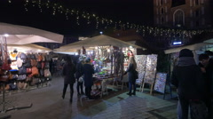 People buying from a toy stall at the Christmas market in Krakow, at night Stock Footage