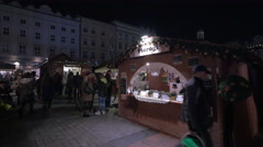 People walking by Pierogi food stall at the Christmas market in Krakow, at night Stock Footage