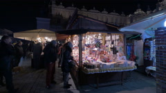 People buying presents from street stalls at the Christmas market in Krakow Stock Footage