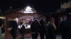 People walking by wooden food stalls at the Christmas market in Krakow, at night Stock Footage