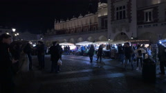 People walking near stalls and the Cloth Hall at the Christmas market, Krakow Stock Footage