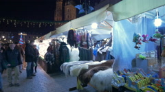 People walking near street stalls with clothes at the Christmas market in Krakow Stock Footage