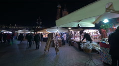 People buying products from street stalls at the Christmas market in Krakow Stock Footage