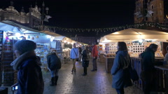 People looking at street stalls at the Christmas market in Krakow, at night Stock Footage