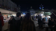 People walking by street stalls at the Christmas market in Krakow, at night Stock Footage