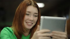 Young woman holding a tablet computer, looking at screen and smiling, saying Stock Footage