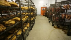 Ready sausages hang in the factory freezer storage waiting to be distributed - stock footage