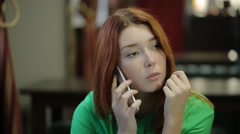 Young red-haired woman takes in hand the smartphone and listen thoughtfully, she Stock Footage
