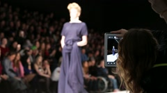 Young woman take pictures with tablet during model catwalk Stock Footage