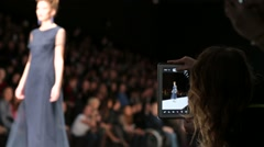 Young woman take pictures with tablet during model catwalk - stock footage