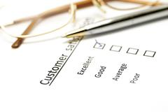 customer satisfaction survey form with the pen and glasses - stock photo