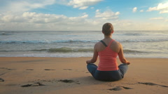 Woman meditating at beach Stock Footage