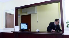 Man looking to file oth documetnts at the concierge desk Stock Footage