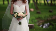 bride in a garden while holding a bouquet in hands - stock footage