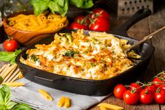 Baked pasta with broccoli, cauliflower, cheese and bechamel sauce - stock photo