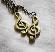 Metal music clef on fabric background Stock Photos