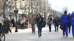Talking on phone in headphones during walking on pedestrian street Stock Footage