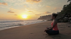 Woman meditating at beach on sunset Stock Footage