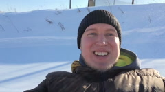 Portrait of a young man coming down the mountain in winter, smiling and looking Stock Footage