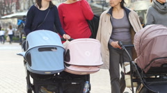 Moms walking with strollers and babies closeup dawn the street Stock Footage