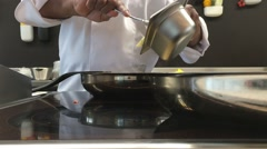 Chef dropping food into a pan Stock Footage
