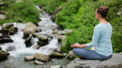 Woman meditating at tropical waterfall Stock Footage