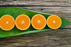 Orange fruit Slices on leaf and wooden background, nature concept Stock Photos