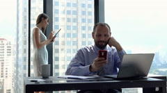 Businesspeople in office, businessman using smartphone - stock footage