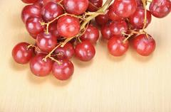 Delicious bunch red seedless crimson grape on wood plank - stock photo
