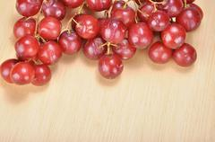 Delicious bunch red seedless crimson grape on wood plank Stock Photos