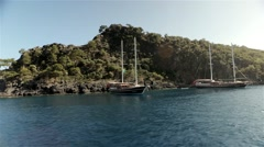 Sailing past two anchored ships at a small island - stock footage