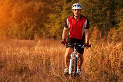 Man is riding a mountain bike in the field - stock photo