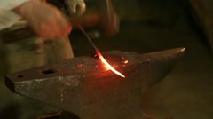Blacksmith hammers on the red-hot piece of iron Stock Footage