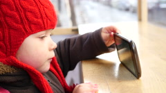 Stock Video Footage of Child in red hat watch cartoons via smartphone during burger break