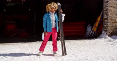 Confident young woman in snowsuit with skis Stock Footage